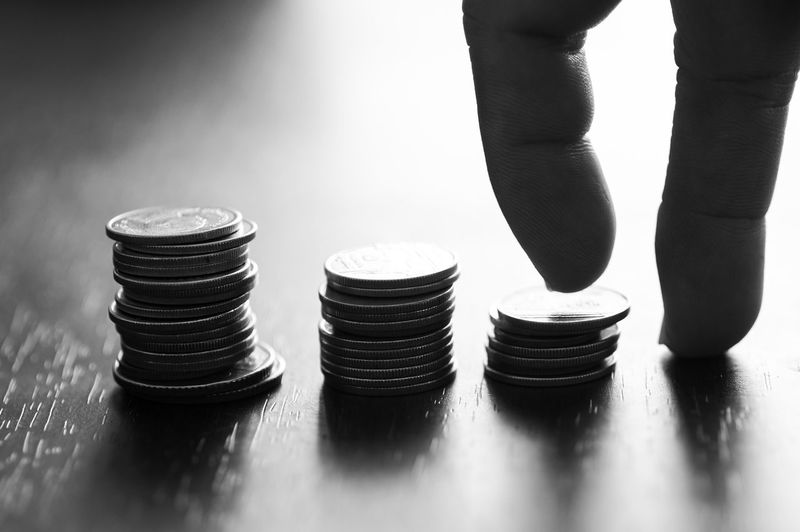 Cropped hands climbing coins stacked on table