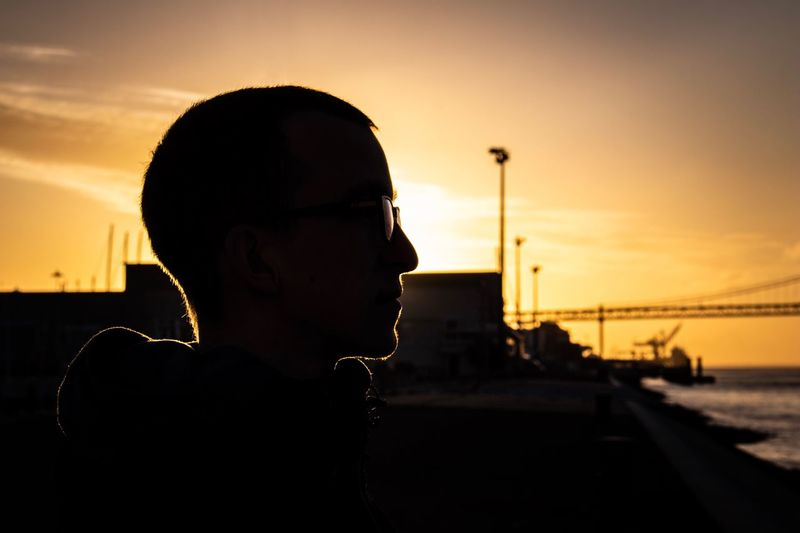 Side view of silhouette teenage boy against sky during sunset
