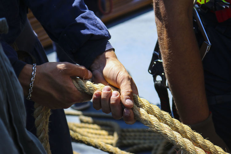 Close-up of person holding ropes