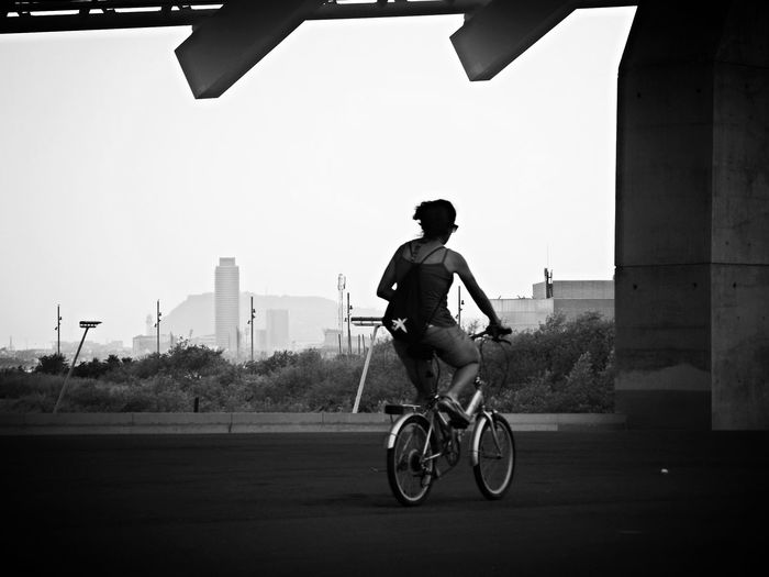Full length rear view of woman cycling on street
