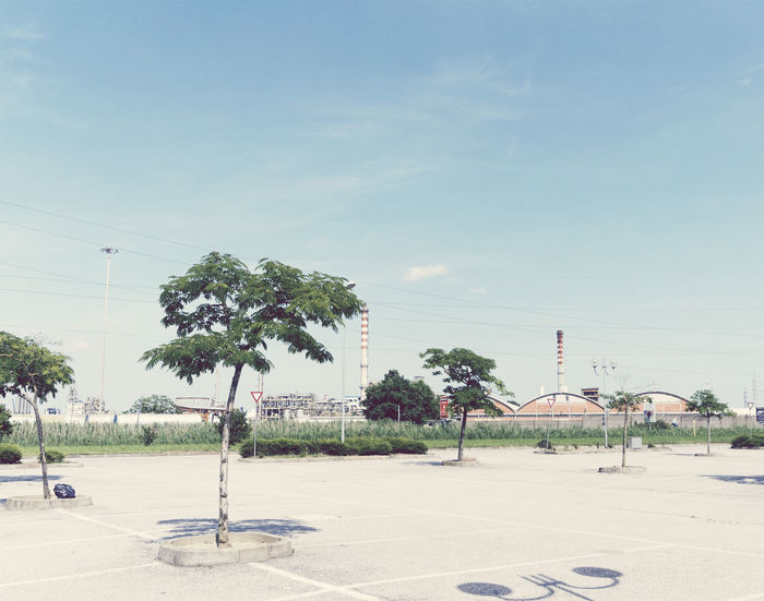 parking lot in suburban area, Italy Absence Asphalt Day Deserted Emptiness Empty Europe Factory Italy No People Nobody Outskirts Parking Parking Lot Power Line  Roadside Sky Suburban Suburbia Tranquility Trees