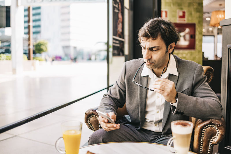 Businessman using smart phone while sitting at cafe