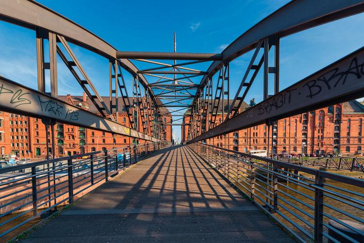 Bridge over footbridge in city against sky
