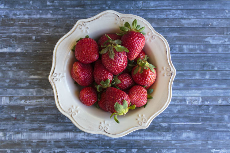 High angle view of strawberries in bowl on blue table