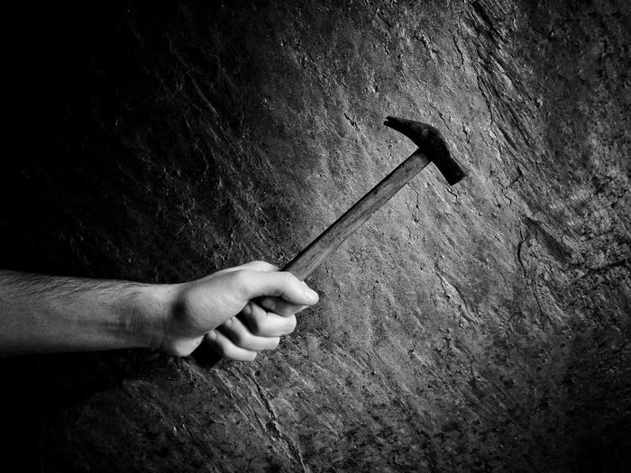 Cropped Hand Of Man Holding Hammer Against Wall