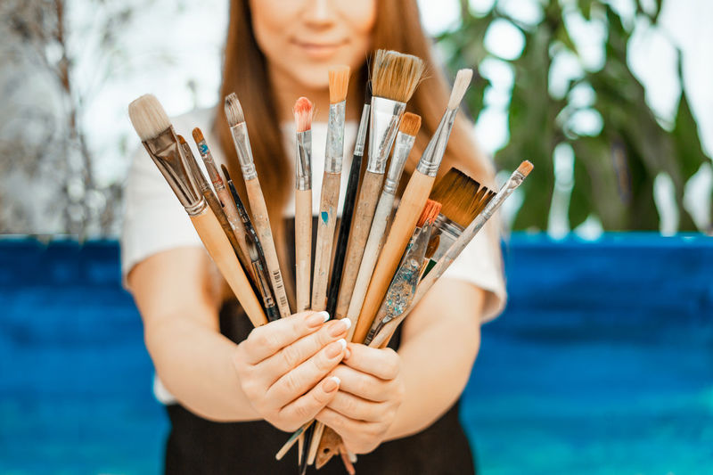 Midsection of woman holding paintbrushes