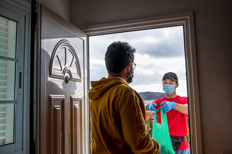 Rear view of man wearing mask taking delivery at door