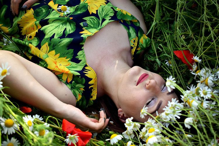 Close-up of woman lying on flower field