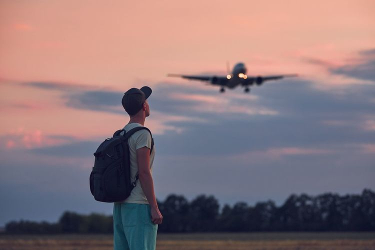 Rear view of man looking at airplane against sky during sunset