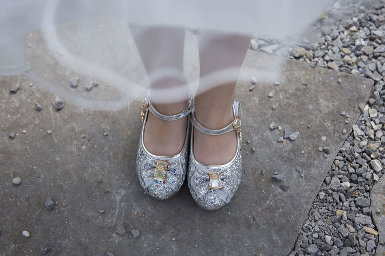 girl standing on ground with diamonds shoes