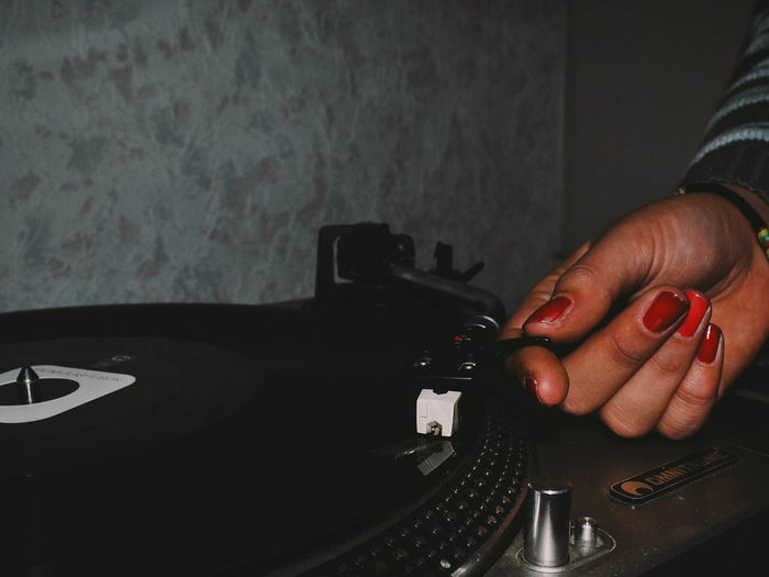 Close-up of hand playing old records
