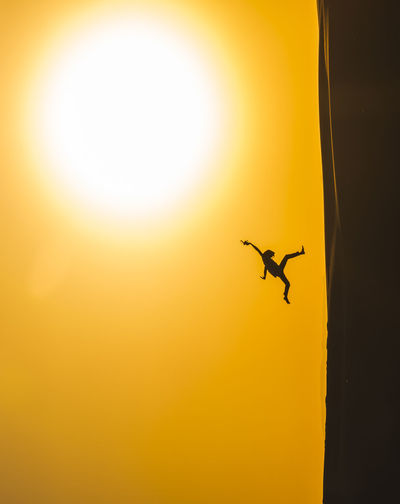 Tilt Shot Of Silhouette Person Jumping Over Sand Dune At Desert Against Orange Sky During Sunset