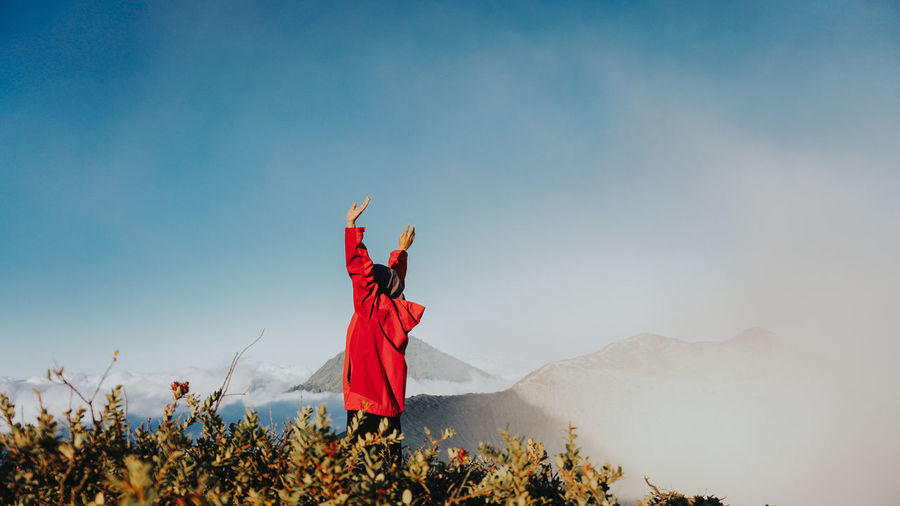 Woman standing on field by mountain against sky