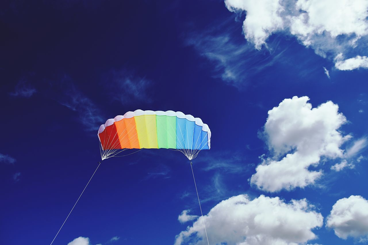 Low angle view of colorful kite flying in sky