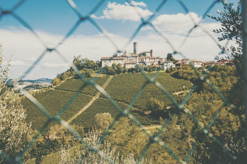 Buildings On Mountains Seen Through Chainlink Fence