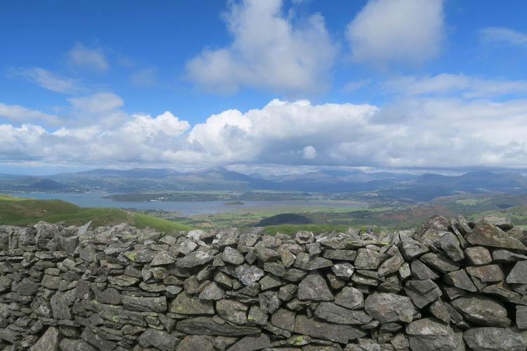 Stack of rocks on landscape against sky