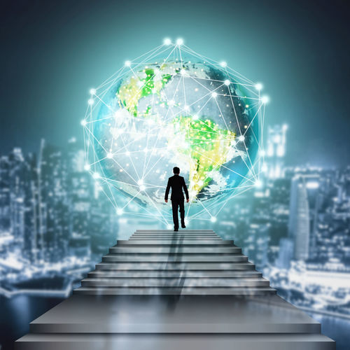 Digital composite image of silhouette businessman leading towards illuminated globe at night