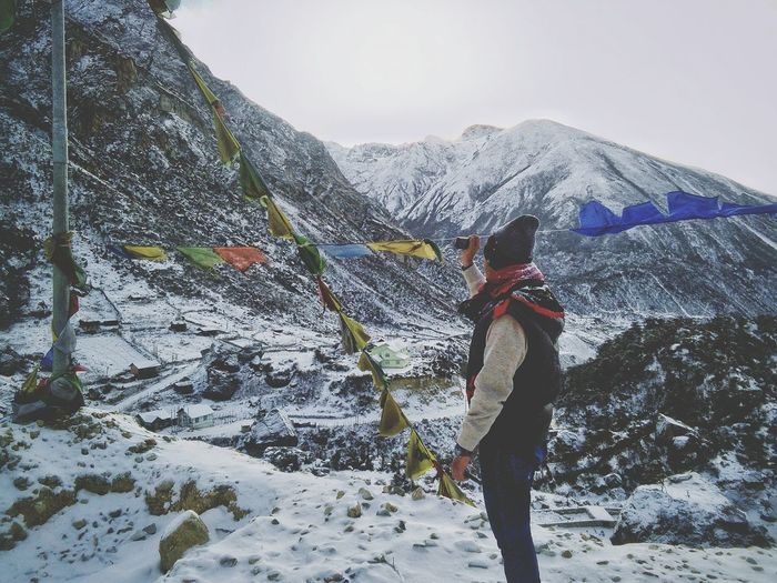 Side view of man standing by prayer flags on snow covered mountain