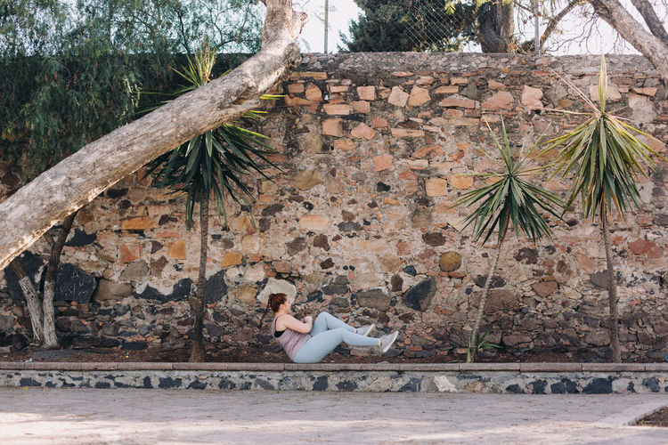 Side view of woman sitting on a wall doing exercise