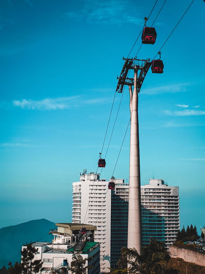 Low angle view of overhead cable car against buildings in genting highlands