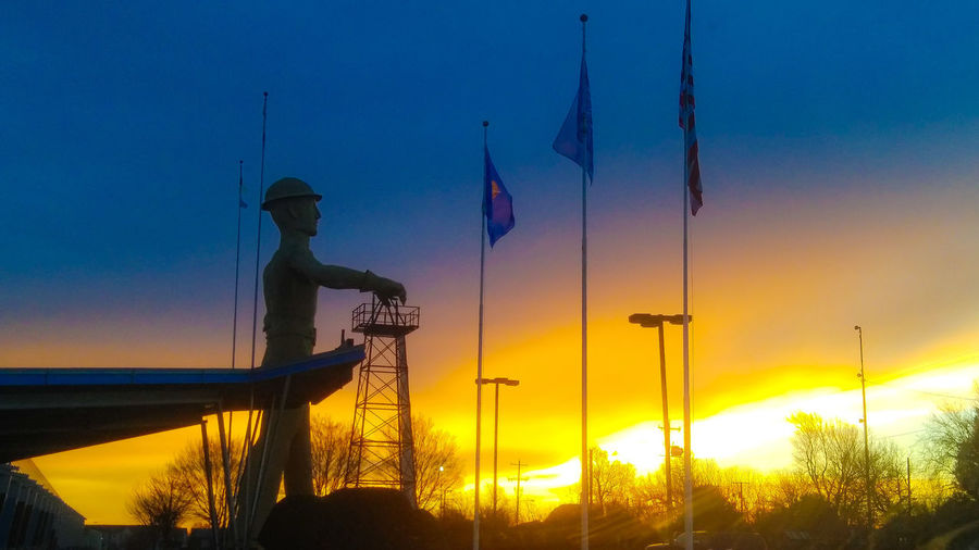 Low angle view of silhouette man against orange sky