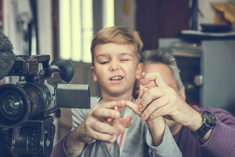 Grandfather teaching boy to use video camera