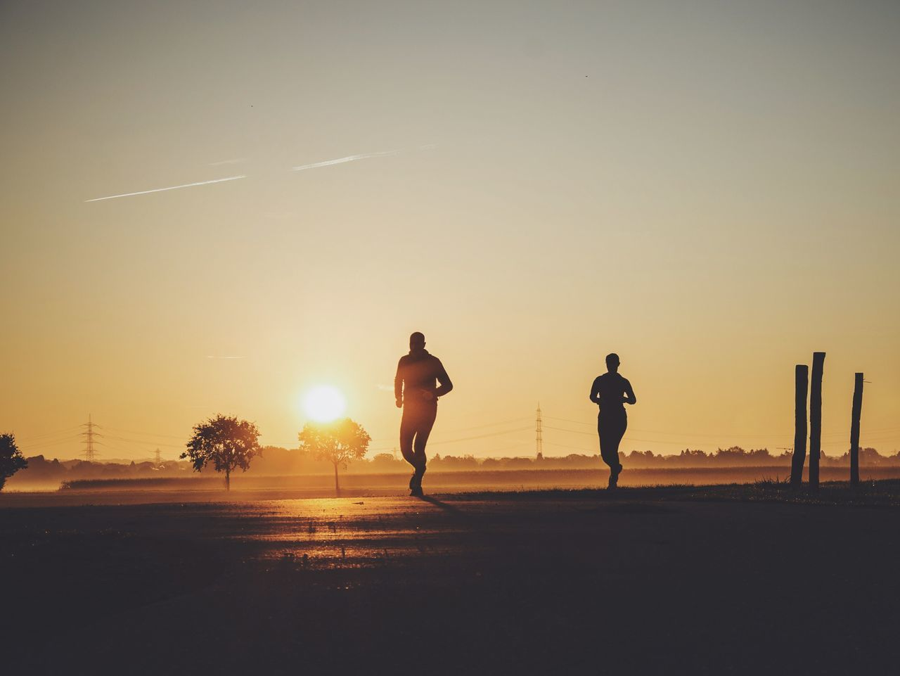 Silhouette people jogging on road against sky during sunset