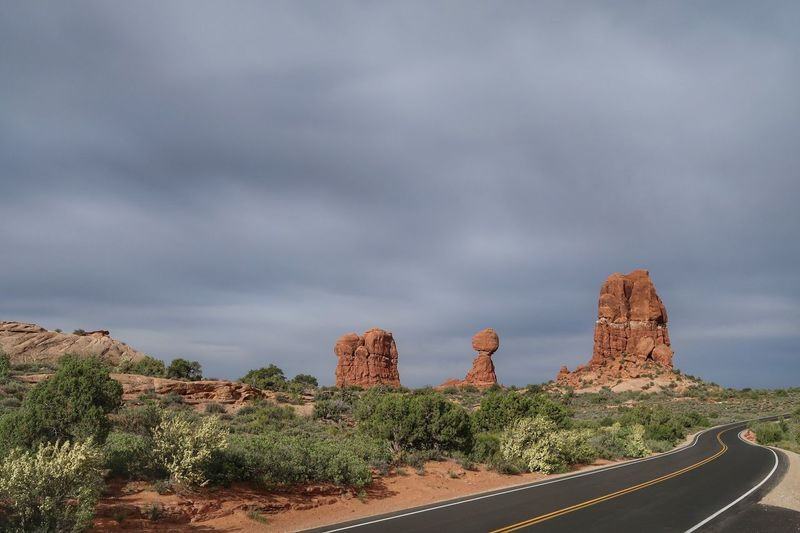 Road leading to rock formation against sky