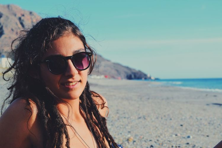 Close-Up Portrait Of Young Woman In Sunglasses At Beach