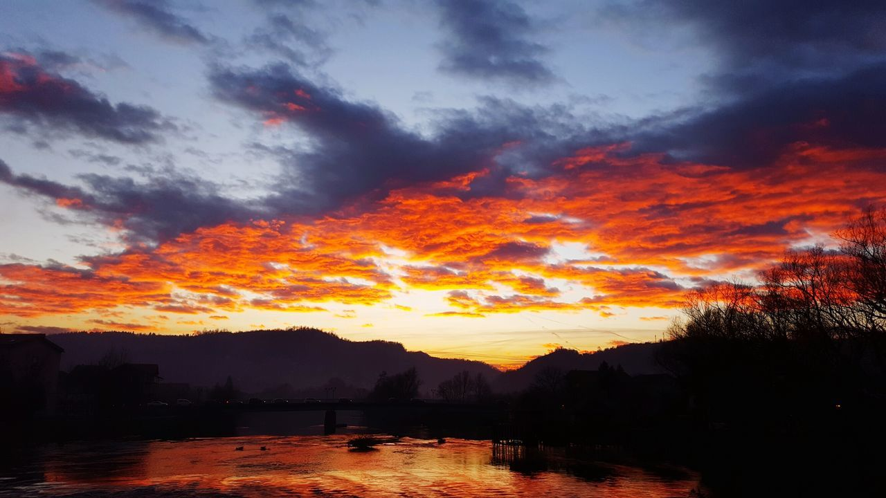 sunset, orange color, silhouette, dramatic sky, beauty in nature, nature, tranquil scene, sky, scenics, cloud - sky, tranquility, tree, no people, outdoors, mountain, water
