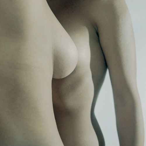 Close-up of naked woman against gray background