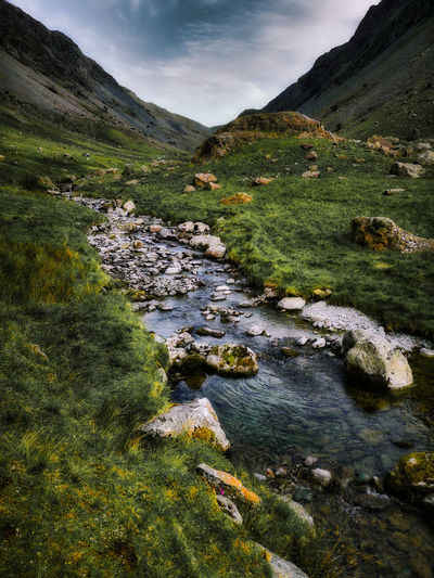 Scenic view of stream amidst rocks against sky