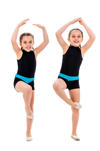 Identical twin girls practice and doing rhythmic gymnastics, white background. Young sister girls are dancing and having fun performing rhythmic gymnastics exercises. Isolated on white background. Acrobat Active Aerobics Athlete Background Balance Ballet Beautiful Caucasian Cheerful Child Children Cute Dance Dancer Exercise Female Fitness Flexibility Flexible Friends Fun Girl Girls Gym Gymnast  Gymnastic Gymnastics Healthy Identical  Isolated Kid Lifestyle Little Performer  Portrait Pose Rhythmic Ribbon Sisters Sport Sports Stretch Studio Training Twin Twins White Young
