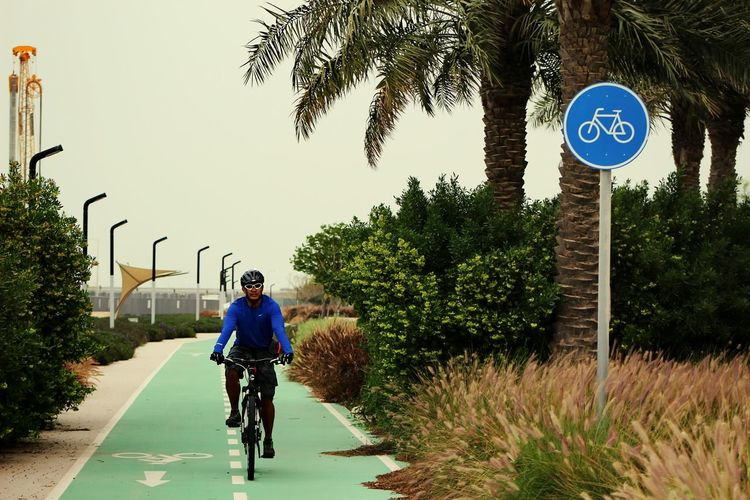 Front view of person cycling on sports track against clear sky