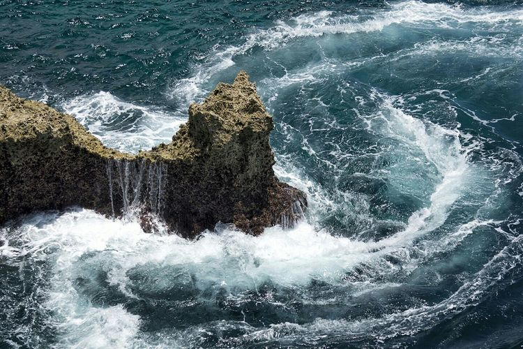 High angle view of wave splashing on rock formation in sea