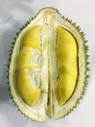 Durian open in half Food And Drink Food Still Life Freshness Healthy Eating SLICE Fruit Table Indoors  No People Close-up Cross Section High Angle View Directly Above Citrus Fruit Malaysia Export Musang King Yellow Ready-to-eat Sweet Food White Background
