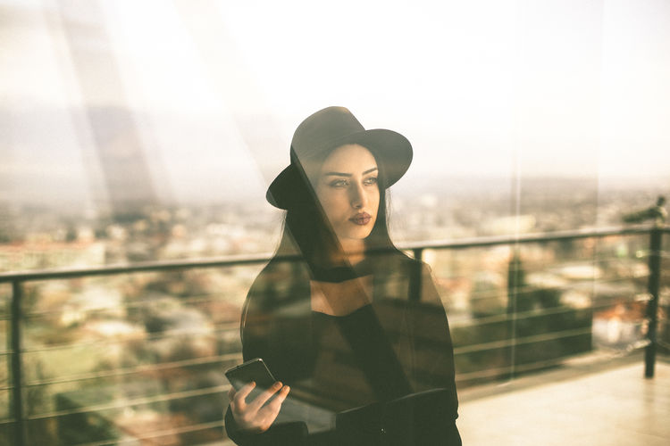 Young Adult One Person Lifestyles Wireless Technology Real People Technology Communication Standing Clothing Beauty Young Women Connection Beautiful Woman Hat Looking Casual Clothing Mobile Phone Glass - Material Portrait Outdoors Contemplation Cityscape