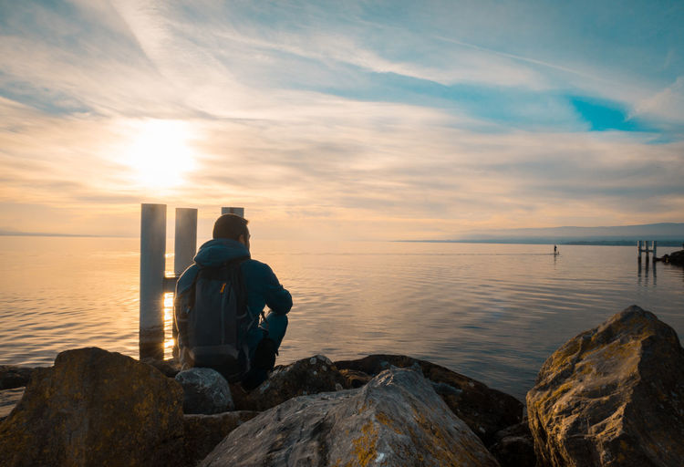 Rear view of man looking at sea while sitting on rock against sky during sunset