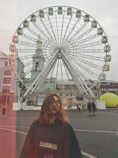 Rear view of woman with ferris wheel in city