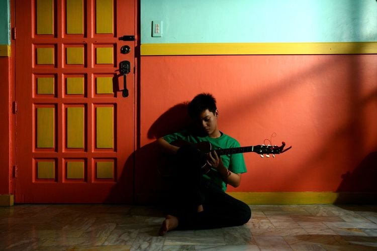 Young man playing guitar while sitting against wall