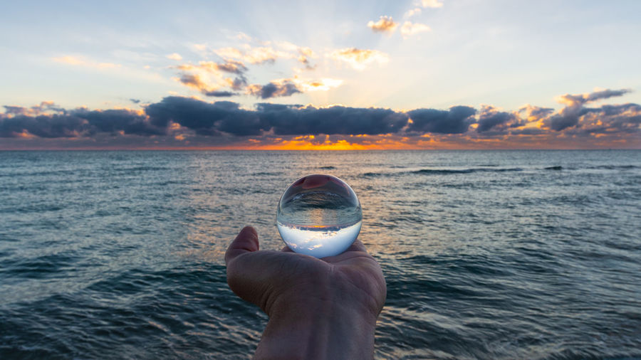 Cropped hand person holding crystal ball by sea against sky during sunset