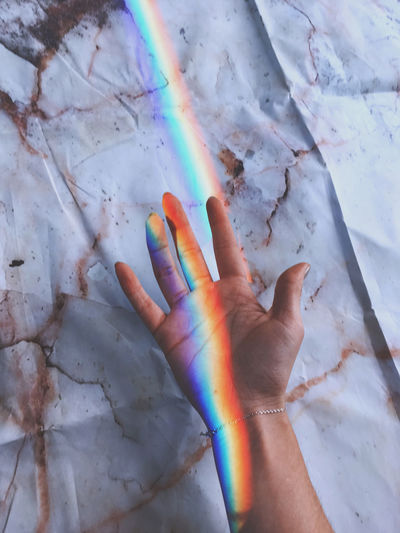 Cropped hand of woman with rainbow against messy paper