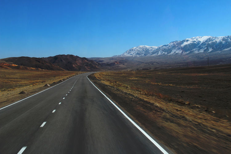 Highway with a turn in the mountains with a snow-covered mountain range, spring, sunny, day