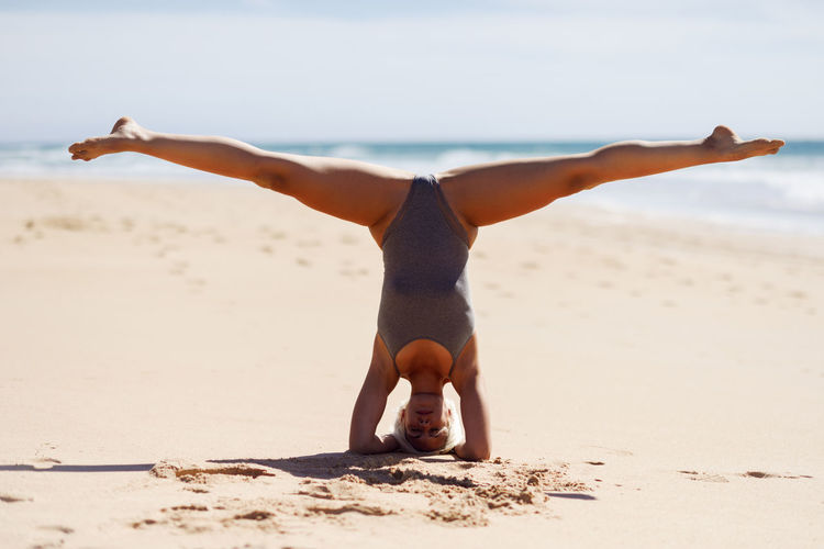 Caucasian woman practicing yoga at seashore. Young female raising arms in the beach in Cadiz, Andalusia, Spain. Land Beach Sand One Person Real People Lifestyles Leisure Activity Sea Exercising Balance Full Length Sky Healthy Lifestyle Nature Sport Water Yoga Day Stretching Human Arm Outdoors Freedom Handstand  Arms Raised Acrobatic Activity Acrobatics  Yoga Yoga Pose