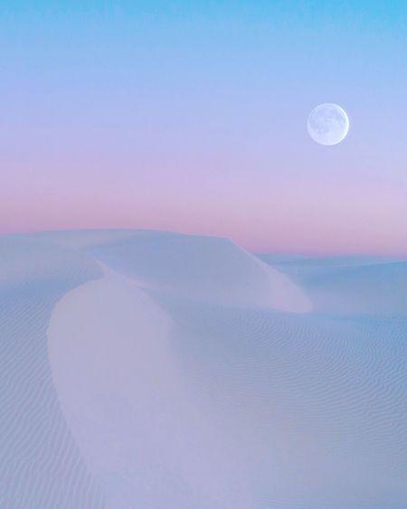 Scenic view of sand dunes in desert against sky during sunset