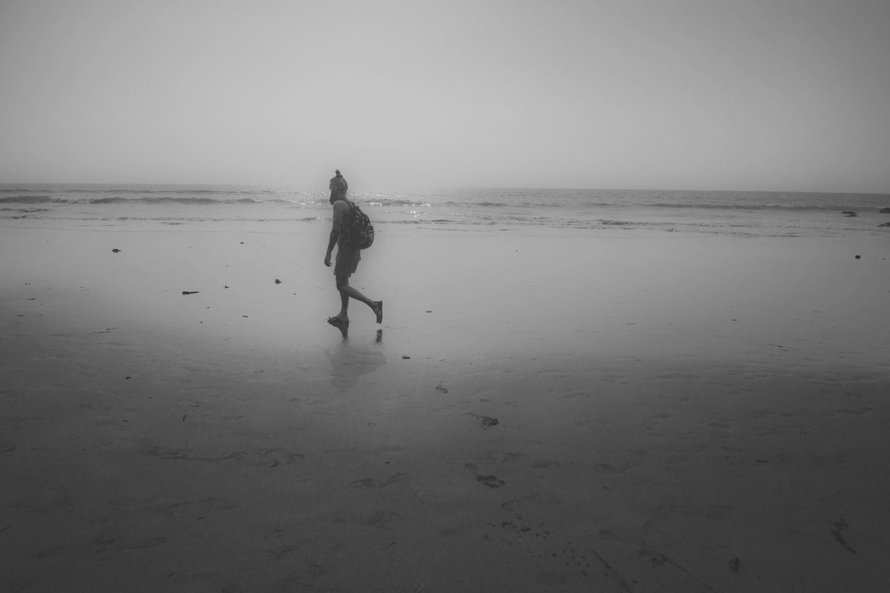 Side View Of Man Walking At Beach Against Clear Sky