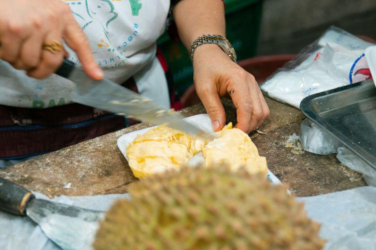 Midsection of man preparing food at market