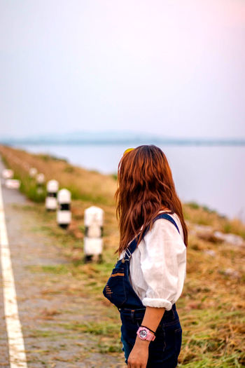 Lovely Women On Vacation Asian Women Dungarees One Person Land Rear View Water Nature Leisure Activity Three Quarter Length Real People Lifestyles Day Sky Casual Clothing Women Adult Focus On Foreground Hairstyle Long Hair Standing Hair Outdoors Wind Horizon Over Water