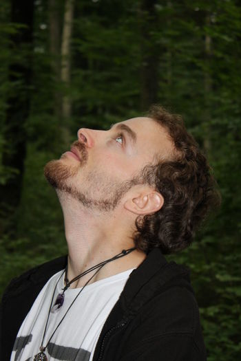 Close-up of man looking up in forest