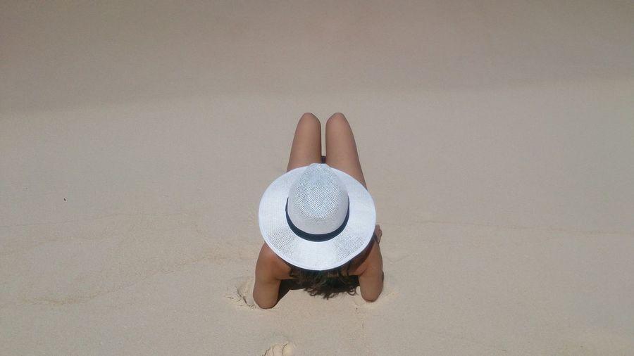 Woman with sun hat lying on beach